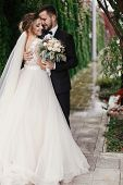 Gorgeous Bride And Stylish Groom Gently Hugging On Background Of Green Trees. Sensual Wedding Couple poster