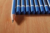 A sharpened pencil among a row of blunt end pencils