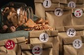 Overturned Glass Jar Full With Gingerbread Christmas Cookies Surrounded By Numbered Paper Bags, A Se poster