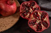 Ripe Pomegranate Fruit And Pomegranate Seeds On Dark Background, Close-up. Healthy Vegetarian Antiox poster