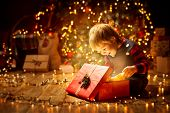 Christmas Child Open Present Gift, Happy Baby Boy Looking To Magic Light In Box, Kid Sitting Front O poster
