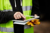 stock photo of personal safety  - construction worker using digital tablet - JPG