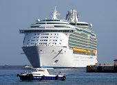 stock photo of cruise ship  - The pilot boat meets the cruise liner that is arriving to Cozumel island Mexico - JPG