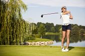 Girl golf player teeing-off with beautiful trees and lake in background, front view.