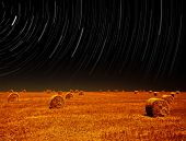 Picture of night landscape of farm field, starry sky above dry haystack on farmland, magic stars slo