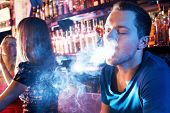 picture of hookah  - Portrait of young man letting smoke out of mouth while smoking hookah - JPG