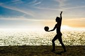 Silhouette Of A Serving Beach Volleyball Girl