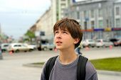 image of teenage boys  - The excited boy looks aside with attention on the street - JPG
