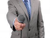 Businessman, journalist or reporter holding a microphone conducting an interview