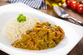 stock photo of chipotle  - Yellow hot curry dish with mixed vegetables served in a white plate - JPG