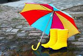 Pair Of Yellow Rubber Boots With An Open Umbrella