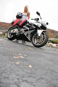 image of crotch-rocket  - A pretty blonde posing with her motorcycle and riding gear - JPG