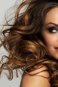Closeup image of beautiful caucasian woman with curls and evening makeup