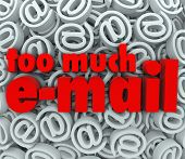 The words Too Much E-Mail on a background of email at symbols and signs to illustrate being flooded