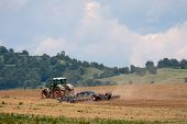 picture of cultivator-harrow  - Tractor plowing field with harrow in the background sky and trees - JPG