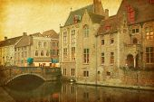 Bruges historic centre, Belgium. Photo in retro style. Paper texture.