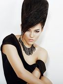 Sentiment. Pensive Bright Woman With Black Updo Hair And Necklace