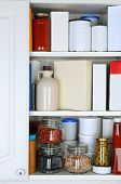 Closeup of a well stocked pantry. One door of the cabinet is open revealing canned goods, condiments