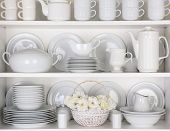 Closeup of white plates and dinnerware in a cupboard. A basket of white roses is centered on the bot