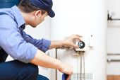picture of handyman  - Plumber repairing an hot - JPG