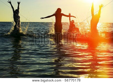 Silhouettes Of People Jumping In Ocean poster