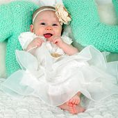 Portrait of very sweet and beautiful little baby child sitting in studio on the soft bed like a bride or princess in funny white and creamy costume with bare feet