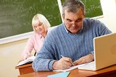 stock photo of senior class  - Senior man in eyeglasses carrying out written task in classroom - JPG