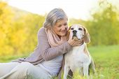 Active senior woman hugs dog
