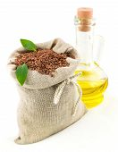 stock photo of flax seed oil  - Macro view of flax seeds in flax sack with leaves and glass bottle of flax oil isolated on white background - JPG