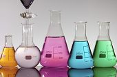 forefront of a laboratory flasks containing brightly colored liquid