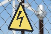 electrical hazard sign placed on a metal fence