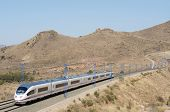 view of a high-speed train crossing a arid landscape in Purroy, Saragossa, Aragon, Spain; AVE Madrid