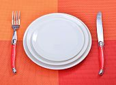 picture of table manners  - White empty plates with fork and knife on a red placemats - JPG