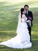 picture of wedding couple  - Wedding couple holding flower bouquet smiling in the golf course - JPG