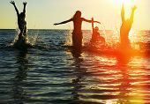 picture of jumping  - Silhouettes of young group of people jumping in ocean at sunset - JPG