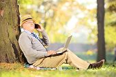 Senior man in park talking on a mobile phone and working on laptop