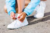 Young healthy girl tie shoelaces of sneakers