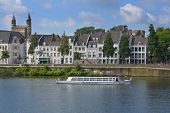 MAASTRICHT, NETHERLANDS - SEPTEMBER 8, 2013: Trip boat with tourists on the Meuse river near the Bas