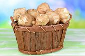 Topinambur roots in wooden basket on table on light background