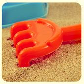 closeup of an orange rake on the sand of a beach or of a sandpit, with a retro effect