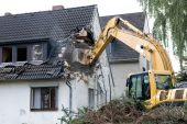 Digger Demolishing House