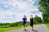 Urban sports - two women or female friends running together for better fitness in the city park on a