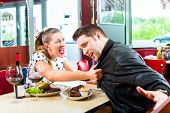 stock photo of diners  - Young couple eating fast food and drinking red wine in a American retro fast food diner argues - JPG