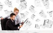 Business man and woman at desk with stock market newspapers concept