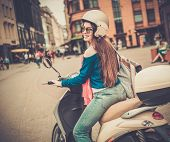 stock photo of scooter  - Young cheerful girl driving scooter in in european city  - JPG