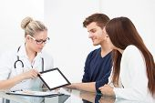 Doctor Showing Report To Couple On Digital Tablet