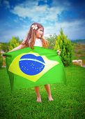 Brazilian football team fan, attractive little girl holding in hands big Brazil national flag, playi