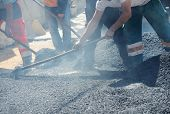 Men hard working on asphalting road with shovels