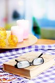 Composition with old book, eye glasses, candles and plaid on bright background