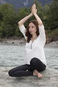 picture of namaste  - Young woman is in namaste pose in spring time by a river - JPG